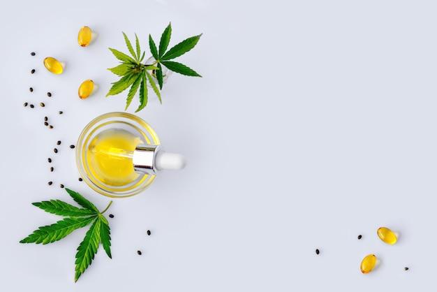 Pharmazeutisches cbd-öl und kapseln auf einem weißen labortisch mit cannabisblättern. das konzept von medizinischem marihuana und alternativer medizin Premium Fotos