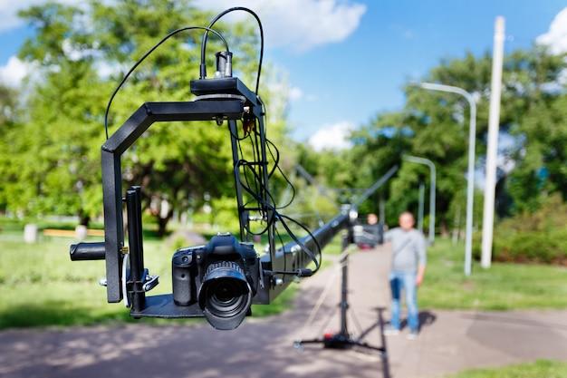 Photocamera auf der plattformnahaufnahme und dem unscharfen videographen, benutzen kamerakran im park am sommertag Premium Fotos