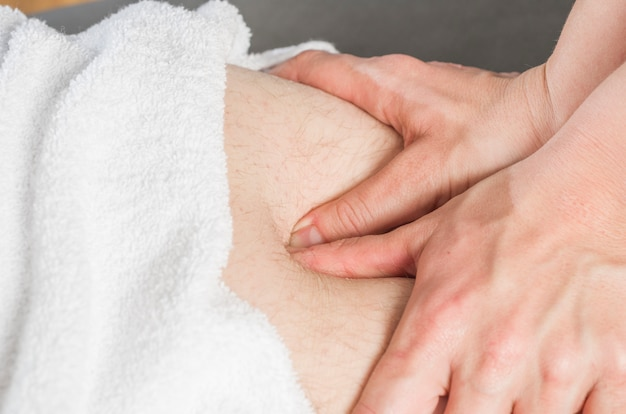 Physiotherapeut, der eine kniesehnenmassage tut, um patienten zu bemannen. Premium Fotos