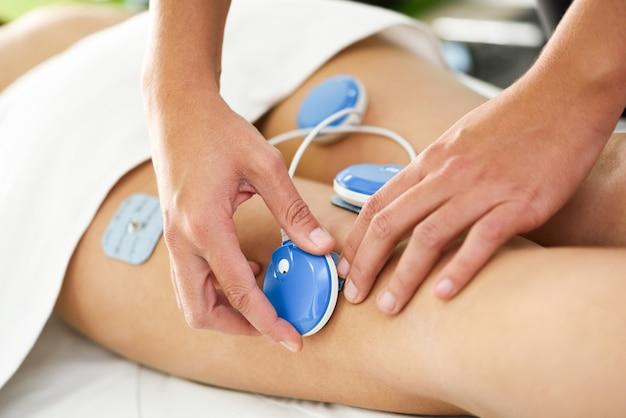 Physiotherapeut, der elektrostimulation in der physiotherapie auf ein bein der jungen frau anwendet. Kostenlose Fotos