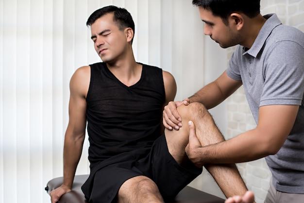 Physiotherapeut, der männlichen patienten des athleten behandelt Premium Fotos