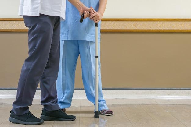 Physiotherapeut in der blauen kleidung, zum sich um die älteren personen in der klinik zu kümmern. Premium Fotos