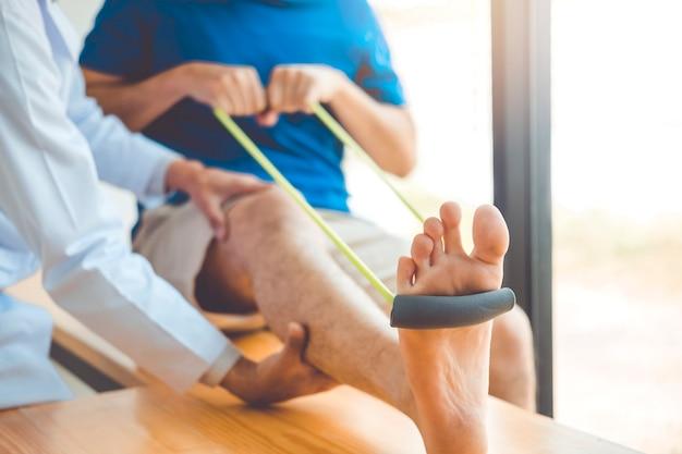 Physiotherapeutenmann, der widerstandband-übungsbehandlung über knie des athleten gibt Premium Fotos
