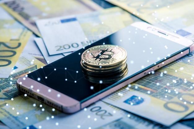 Physische bitcoin-münze auf dem telefonbildschirm auf dem hintergrund von eurobanknoten. kryptowährung und blockchain in unserem leben Premium Fotos