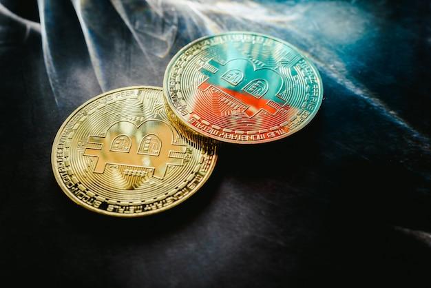Physische bitcoin-münzen beleuchtet durch helle strahlen mit dunklem hintergrund. Premium Fotos