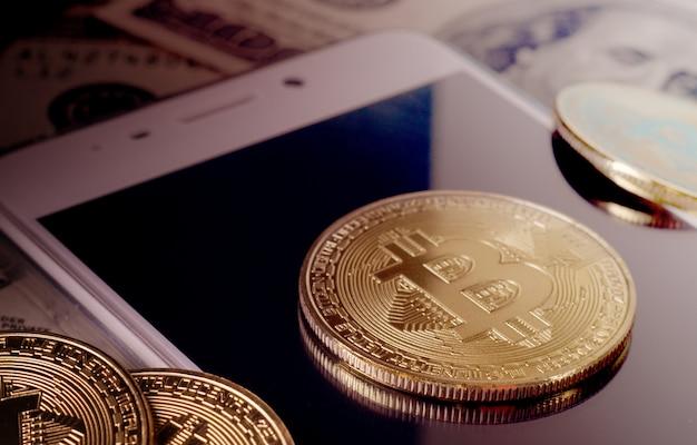 Physische gold-bitcoin-münze gegen dollarscheine und smartphone auf einem purpurroten hintergrund. Premium Fotos