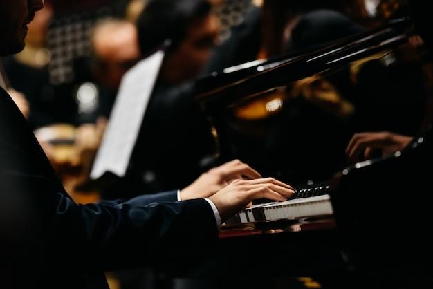 Pianist, der ein stück auf einem flügel bei einem konzert spielt, von der seite gesehen. Premium Fotos