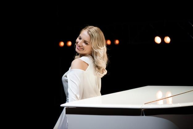 Pianist posiert in der nähe von weißem klavier auf der bühne. Premium Fotos