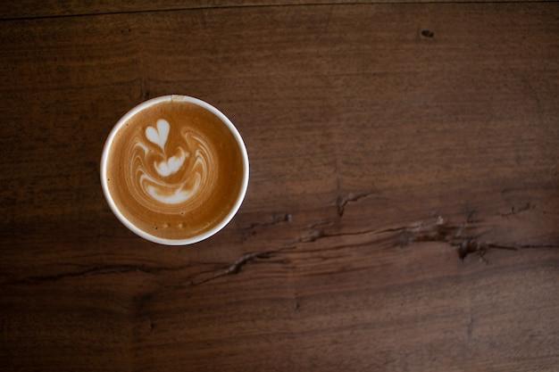 Piccolo latte-kunst in der papierschale auf hölzernem schreibtisch Premium Fotos