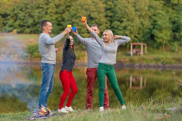 Picknick mit freunden herein am see nahe feuer. firmenfreunde beim picknick Premium Fotos