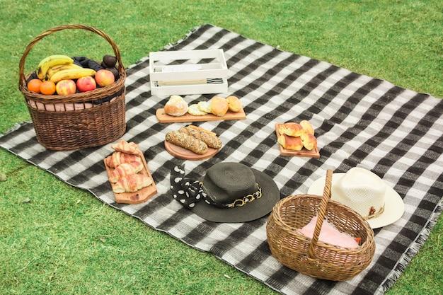 Picknickkorb mit frischen früchten; gebackene brote und hut auf decke über dem grünen gras Kostenlose Fotos
