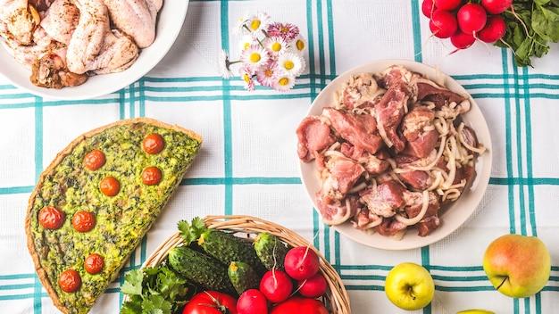 Picknicktisch mit rohem mariniertem fleisch, gemüse und kuchen. sommerzeit. Premium Fotos