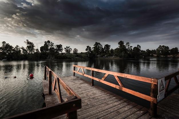 Pier mit der hölzernen balustrade belichtet durch die sonnenuntergangsonne Premium Fotos