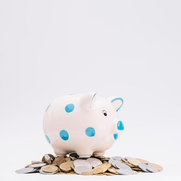 Piggybank über den münzen gegen weißen hintergrund Kostenlose Fotos