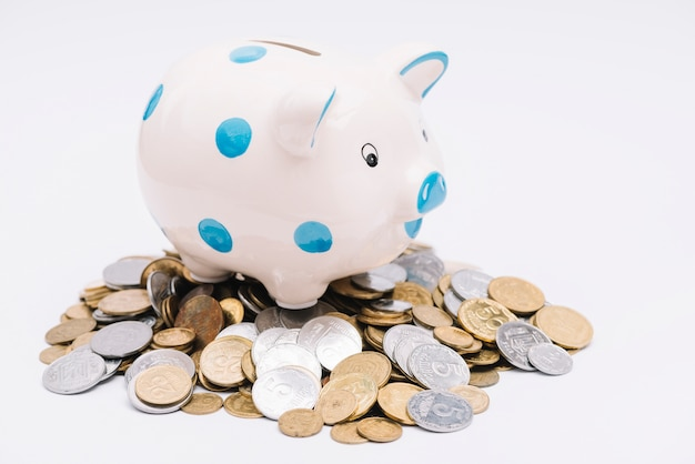 Piggybank über vielen münzen auf weißem hintergrund Kostenlose Fotos