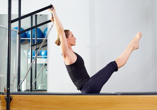 Pilates-frau in der reformer-teaserübung an der turnhalle Premium Fotos