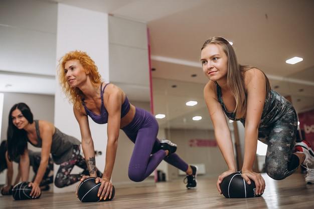 Pilates-gruppe, die in einer turnhalle ausarbeitet Kostenlose Fotos