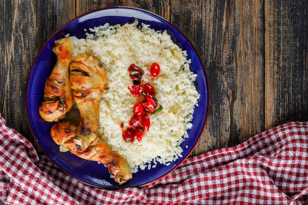 Pilaw in einem teller mit hühnerfleisch, preiselbeeren auf holz und küchentuch Kostenlose Fotos