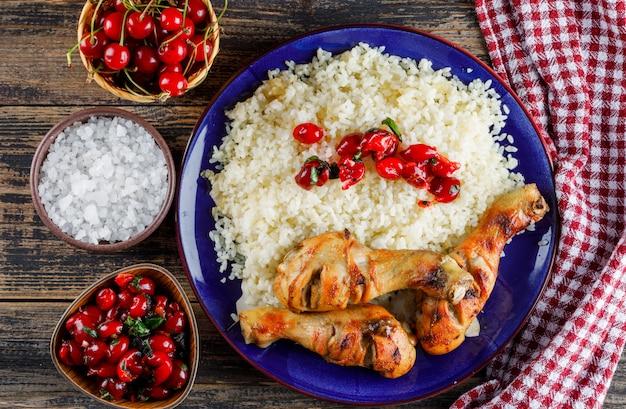 Pilaw mit hühnerfleisch, kirsche, salz in einem teller auf holz und küchentuch. Kostenlose Fotos