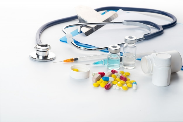 Pillen, die aus pilleflaschenspritzenthermometer und -stethoskop auf weißem hintergrund heraus verschüttet werden Premium Fotos