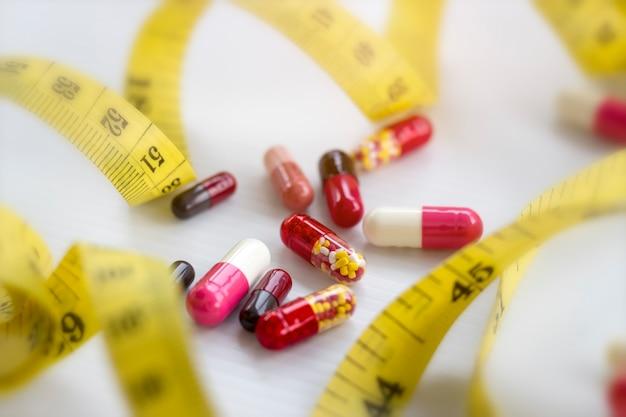 Pillen, kapsel mit messendem band auf weiß Premium Fotos