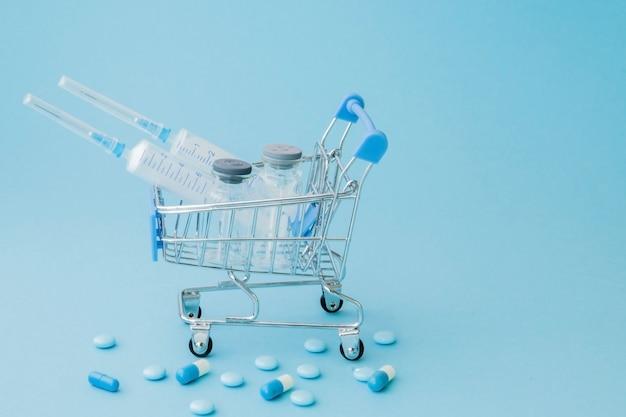 Pillen und medizinische einspritzung in der einkaufslaufkatze auf blauem hintergrund. kreative idee für gesundheitswesenkosten, drogerie, krankenversicherung und pharmaunternehmengeschäftskonzept. kopieren sie platz Premium Fotos