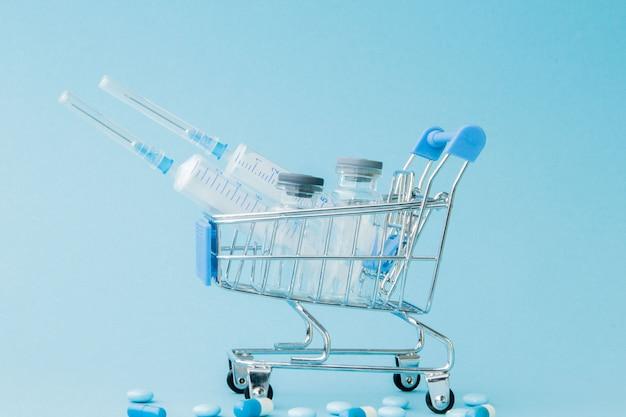 Pillen und medizinische injektion im einkaufswagen Premium Fotos
