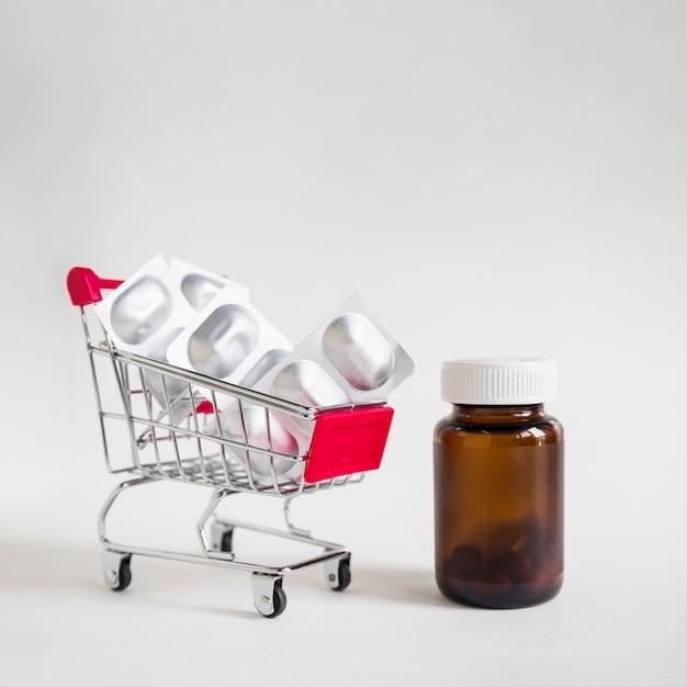 Pillenblasen im einkaufswagen mit glasflasche auf weißem hintergrund Kostenlose Fotos