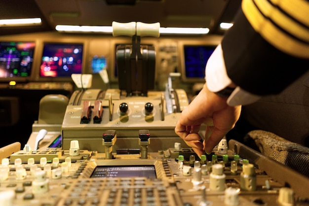 Pilot in uniform im flugzeugcockpit stimmt radio panel. Premium Fotos