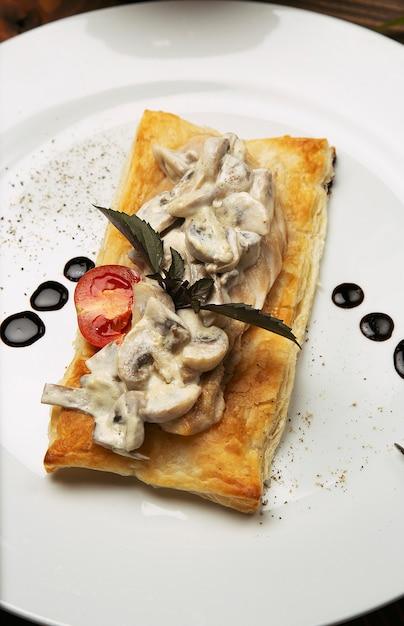 Pilz sautiert, hähnchen-stroganoff auf einem stück brot. antipasta in einer verzierten weißen platte mit tischbesteck auf holztisch Kostenlose Fotos