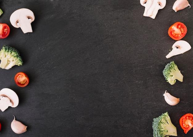 Pilz; tomaten; brokkoli und knoblauchzehen auf schwarzem hintergrund mit platz für das schreiben des textes Kostenlose Fotos