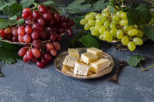 Pinsel aus roten trauben in einem silbernen teller und ein pinsel aus hellen trauben, eine rebe, käse in einem silbernen teller und eine gabel Premium Fotos