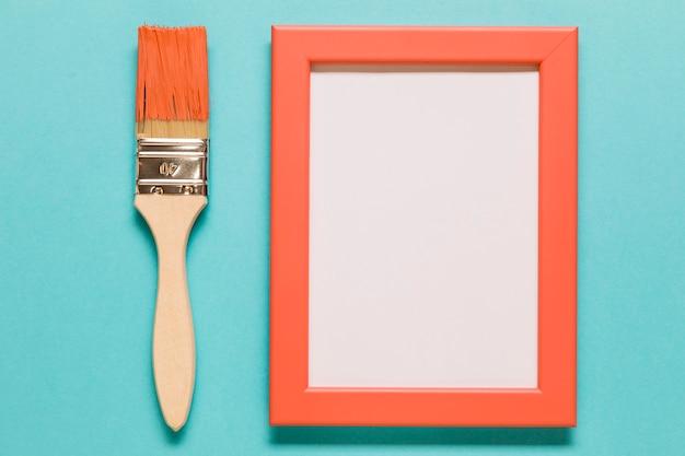 Pinsel und leerer rahmen auf blauem hintergrund Kostenlose Fotos