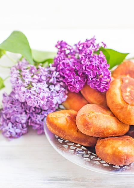 Piroshki - russisch gebackener blätterteig mit kohlfüllungen und fliederstrauß. traditioneller russischer kohl gefüllt gebackenes gebäck. magere kuchen mit kohl. schöne hausgemachte kuchen mit kohl Premium Fotos