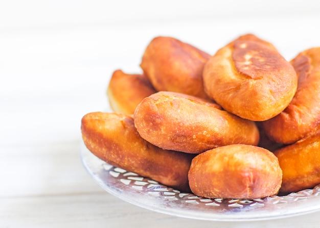 Piroshki - russischer blätterteig mit kohlfüllungen. traditioneller russischer kohl gefüllt gebackenes gebäck. magere kuchen mit kohl. schöne hausgemachte kuchen mit kohl in metallschalen auf weiß Premium Fotos
