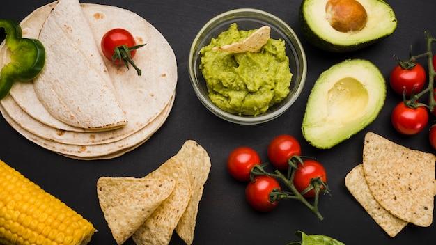 Pita in der nähe von gemüse und soße mit nachos Kostenlose Fotos