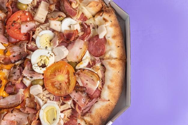 Pizza auf dem tisch in lila farbe Premium Fotos