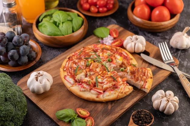 Pizza auf einen holzteller gelegt. Kostenlose Fotos
