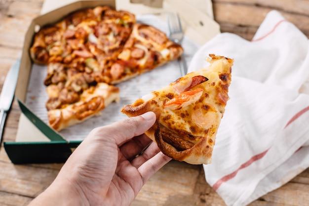 Pizza im papierkasten auf holztisch Premium Fotos