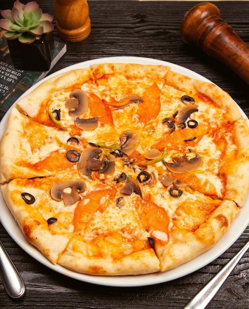 Pizza margarita mit schwarzen oliven, pilzen, tomatensauce, tomatenscheiben und parmesankäseparmesankäse auf weißer platte. Kostenlose Fotos