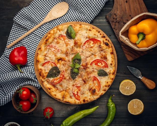 Pizza mit grünen basilikum- und tomatenscheiben. Kostenlose Fotos