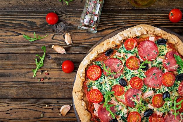 Pizza mit salami, tomaten, oliven und käse auf einem teig mit vollkornmehl. italienisches essen. draufsicht. flach liegen. Premium Fotos