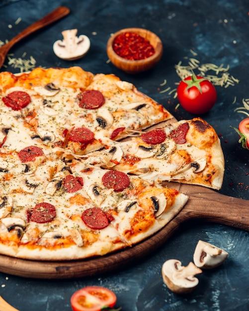 Pizza mit salami und pilzen Kostenlose Fotos