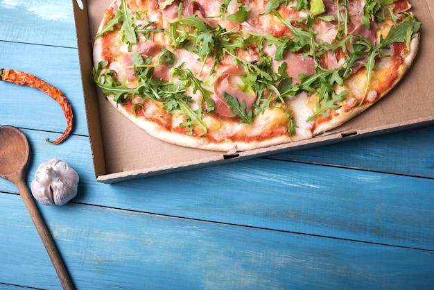Pizza mit speck und arugula verlässt in der pappschachtel mit rotem paprika und knoblauchknolle über holztisch Kostenlose Fotos