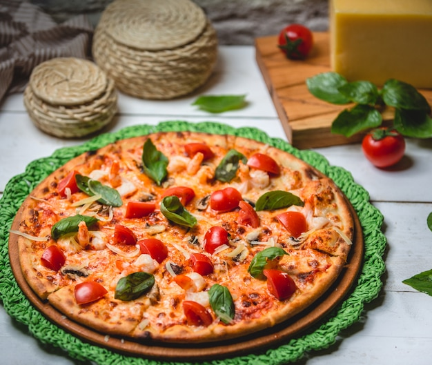Pizza mit tomaten und basilikum auf dem tisch Kostenlose Fotos