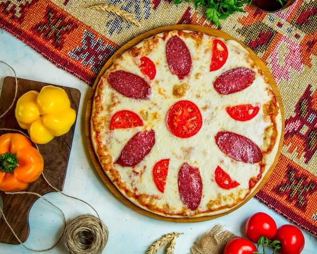 Pizza mit würstchen und tomaten belegt Kostenlose Fotos