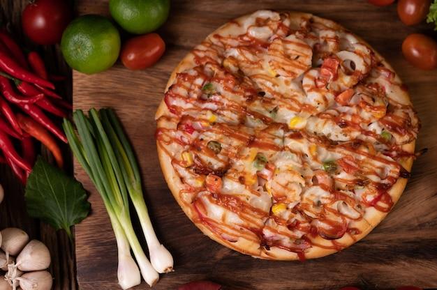 Pizza mit wurst, mais, bohnen, garnelen und speck auf einem holzteller Kostenlose Fotos