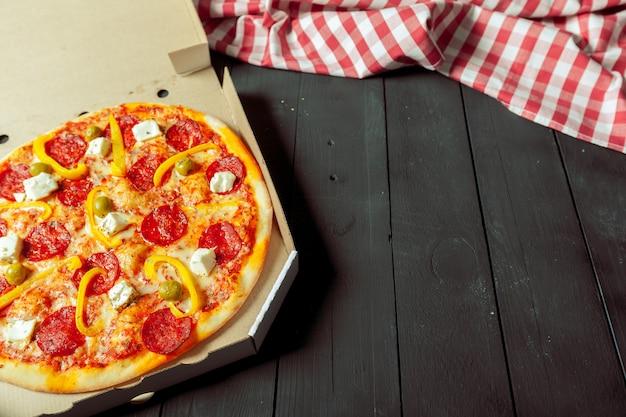 Pizza wird in der schachtel auf dem tisch neben dem stoff geliefert Premium Fotos