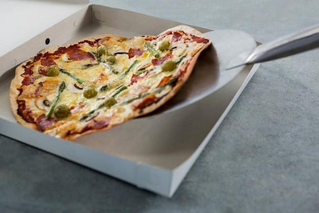 Pizza wird in eine schachtel gelegt Premium Fotos