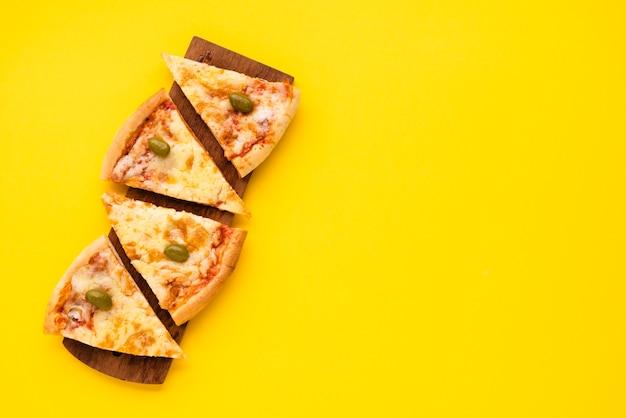 Pizzascheibe vereinbart auf hölzerner platte über gelbem hintergrund Kostenlose Fotos